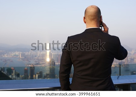 Back view of man entrepreneur is calling via smart phone, while is standing on a building roof with view of business center in New York. Male managing director phoning via cellphone during work break  - stock photo