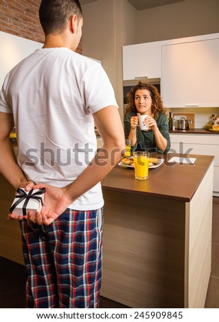 Back view of man hiding a gift box behind his back and his surprised girlfriend waiting while having breakfast on the home kitchen - stock photo