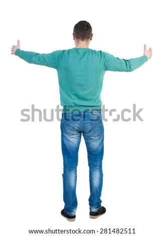 Back view of man in jeans. Standing young guy. Rear view people collection.  backside view of person.  Isolated over white background. The guy tries to put her arms around something big. - stock photo