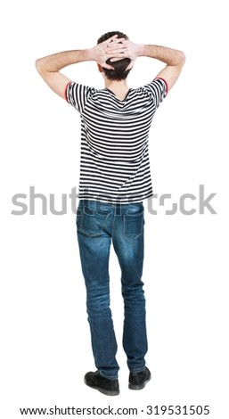 Back view of man in jeans. Standing young guy. Rear view people collection.  backside view of person.  Isolated over white background. The guy in the striped shirt sits with his hands behind his head. - stock photo