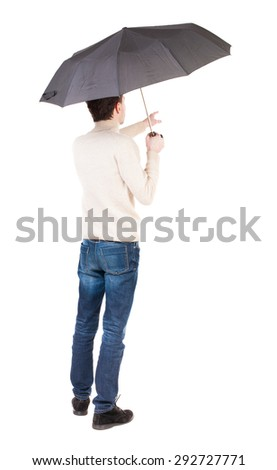 Back view of man in jeans under an umbrella. Standing young guy. Rear view people collection. A guy in a white warm sweater hiding from the rain under an umbrella and points vnebo. - stock photo