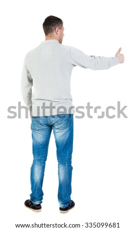 Back view of  man in shirt shows thumbs up.   Rear view people collection.  backside view of person.  Isolated over white background.  The guy who shows a sign to the left... - stock photo