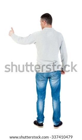 Back view of  man in shirt shows thumbs up.   Rear view people collection.  backside view of person.  Isolated over white background.  A guy in a gray jacket showing thumbs up with his right hand. - stock photo