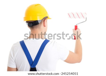 back view of man painter in workwear with paintbrush isolated on white background - stock photo
