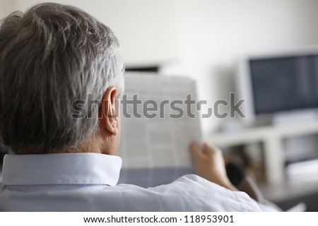 Back view of man reading newspaper at home - stock photo
