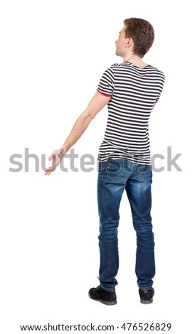 Back view of man . Standing young guy. Curly boy in a striped vest emotionally gesticulates.