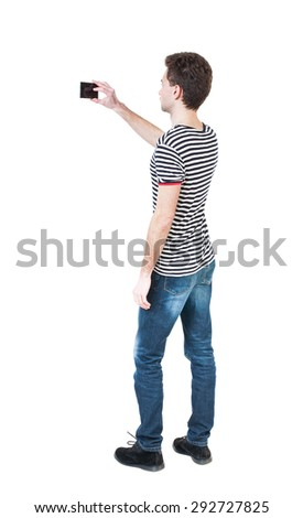 Back view of man with tablet. Standing young guy. Rear view people collection.  backside view of person.  Isolated over white background. The guy in the striped shirt photographs... - stock photo