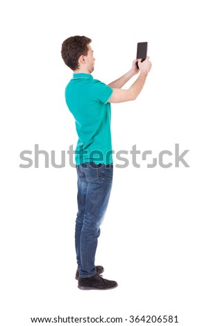 Back view of man with tablet. Standing young guy. Rear view people collection.  backside view of person.  Isolated over white background. Curly guy focused photographs. - stock photo