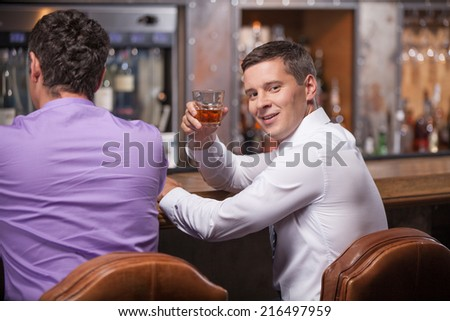 back view of men sitting at counter. waist up of two friends sitting in bar and drinking whisky - stock photo