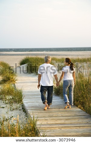 Back view of mid-adult Caucasian couple walking down walkway to beach. - stock photo