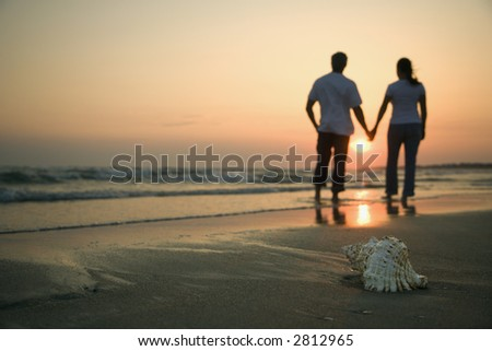 Back view of mid-adult couple holding hands walking on beach with seashell in foreground. - stock photo