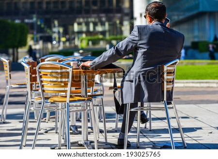 Back view of Modern businessman drinking a coffee while working outdoor with mobile - stock photo