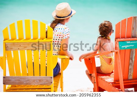 Back view of mother and daughter family sitting on colorful wooden chairs at tropical beach enjoying summer vacation - stock photo