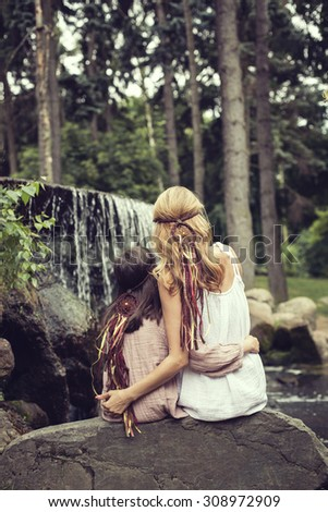 Back view of mother and daughter staring at the forest - stock photo