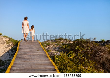 Back view of mother and daughter walking along a wooden path - stock photo