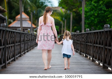 Back view of mother and daughter walking along wooden jetty - stock photo