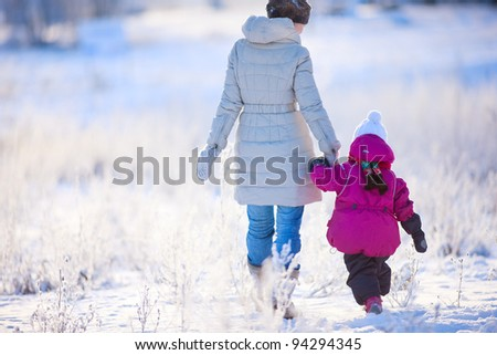 Back view of mother and daughter walking on winter day - stock photo