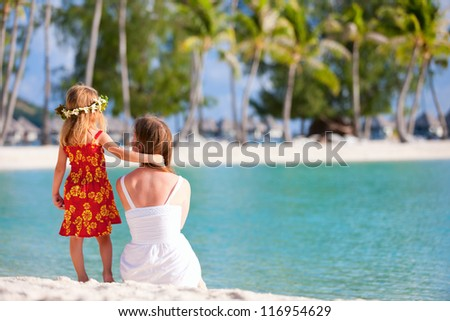 Back view of mother and daughter wearing Polynesian dress on a tropical beach