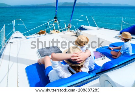 Back view of mother and her kids relaxing having great time sailing at luxury yacht or catamaran boat - stock photo