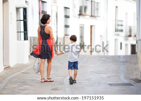 Back view of mother and her little son outdoors in city on beautiful summer day - stock photo
