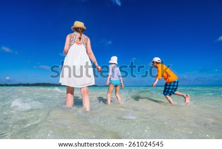 Back view of mother and two kids walking on shallow water at tropical beach enjoying summer vacation - stock photo