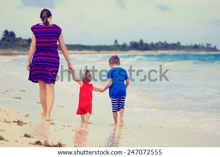 back view of mother and two kids walking on the beach - stock photo