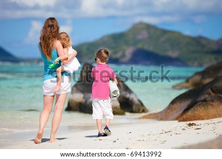 Back view of mother and two small kids walking along tropical beach - stock photo