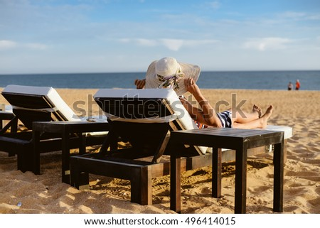 Back view of mother with kids relaxing on the beach, sunny outside background. Woman on recreational leisure tropic vacation