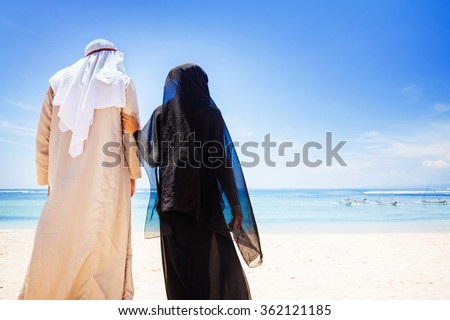 back view of muslim couple on a beach wearing traditional dress - stock photo
