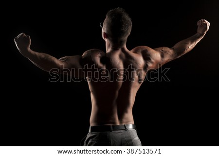 back view of naked muscular man in pants on black