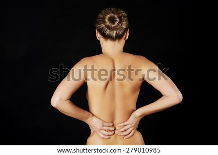 Back view of naked woman touching her back.