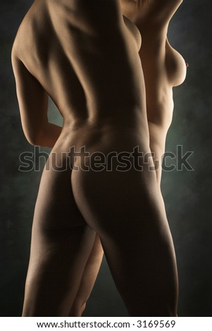 Back view of nude Hispanic and Caucasian women standing together. - stock photo