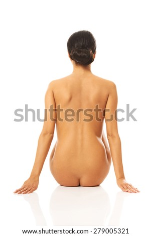 Back view of nude woman sitting supports the floor. - stock photo