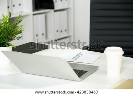 Back view of office desktop with open laptop, coffee cup, plant and notepads