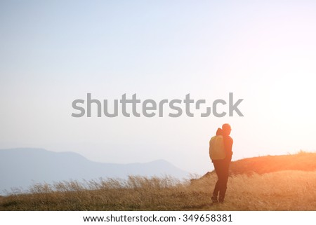 Back view of one lonely traveller going by walk with backpack in mountains with deep dry spikelet grass at sunset windy weather outdoor on natural background copyspace, horizontal picture - stock photo