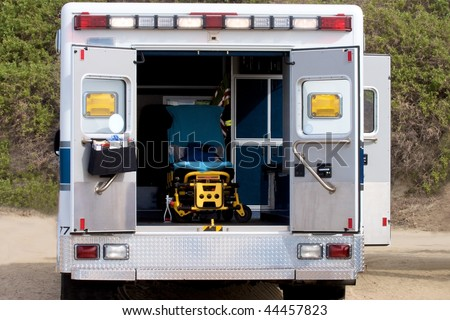 Back view of paramedics van with open doors and gurney inside - stock photo