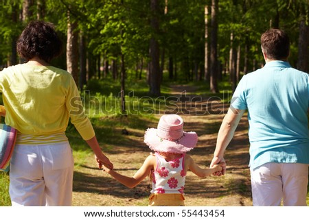 Back view of parents and their daughter walking in the forest on summer day