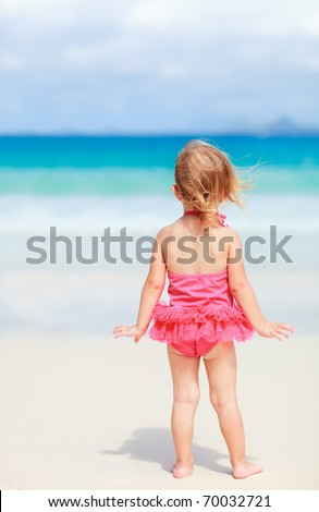 Back view of playful toddler girl on white sand beach - stock photo