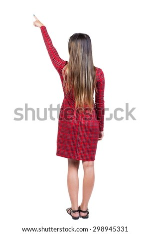 Back view of  pointing woman. beautiful girl. Rear view people collection.  backside view of person.   Long-haired girl in a red plaid dress standing shows a finger up to the right. - stock photo