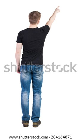 Back view of  pointing young men in  t-shirt and jeans. Young guy  gesture. Rear view people collection.    Isolated over white background. A man in a black jacket and is showing one of his hands up.  - stock photo