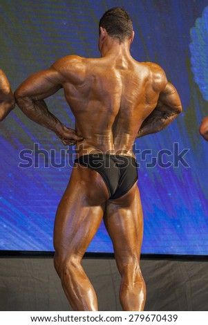 Back View of Professional Male Caucasian Bodybuilder Performing on Stage. Vertical Image Composition - stock photo