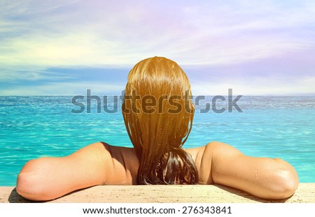 Back view of relaxed woman in blue water - stock photo