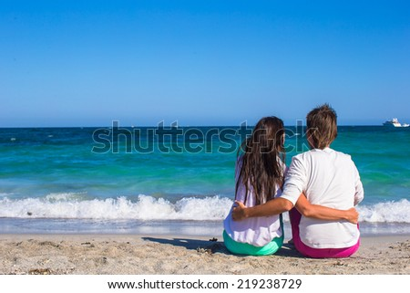 Back view of romantic couple at white beach during tropical vacation - stock photo