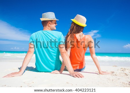 back view of romantic couple in bright clothes enjoying sunny day at tropical beach - stock photo