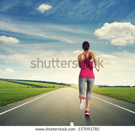 back view of running woman on the road - stock photo