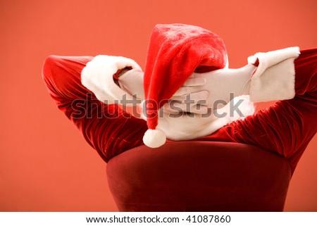 Back view of Santa Claus keeping his hands behind head - stock photo