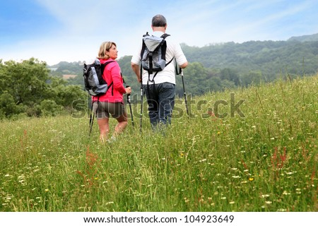 Back view of senior couple hiking in countryside - stock photo