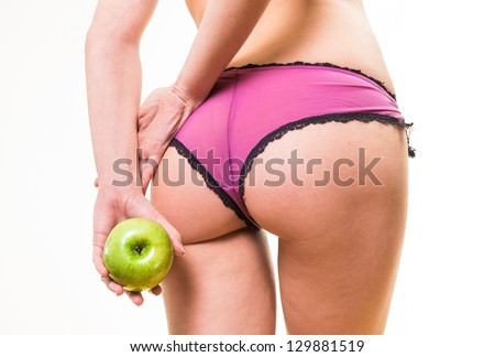 back view of sensual female with nice buttocks and apple in hand - stock photo