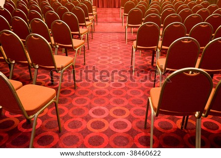 Back view of several rows of red armchairs in conference hall
