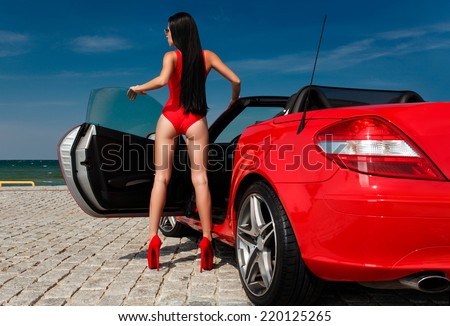 back view of sexy young woman in red bodysuit posing with red cabriolet against sea and sky background - stock photo